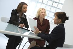Businesswomen at meeting. Businesswomen seated around table for meeting stock images