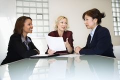 Businesswomen meeting. Three businesswomen sitting at office desk having meeting and discussing paperwork Royalty Free Stock Photo