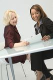 Businesswomen Meeting. A metaphorical image of two happy businesswomen in a meeting discussing a project stock photo