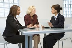 Businesswomen in meeting. Businesswomen sitting around table in a meeting stock image
