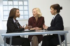Businesswomen in meeting. A metaphorical image of the team of three businesswomen discussing about a business deal in an office stock photo