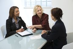 Businesswomen in meeting. A view of three businesswomen around a table for a meeting royalty free stock images