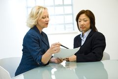 Businesswomen in meeting. Two middle-aged businesswomen discussing a project in an office Royalty Free Stock Photography