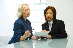 Businesswomen in Meeting. A metaphorical image of two businesswomen in a meeting discussing a project stock photography