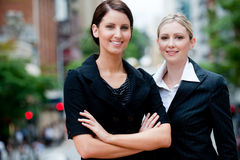 Businesswomen Outside. Two young professional businesswomen standing in the city (only one in focus Stock Photo