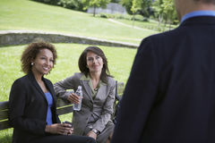 Businesswomen On Park Bench Looks At Businessman Royalty Free Stock Image