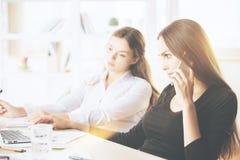 Businesswomen on phone using laptop Royalty Free Stock Image