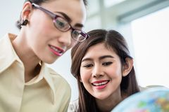 Businesswomen planning world dominance in their office Royalty Free Stock Image
