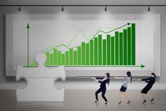 Businesswomen pull puzzle on profit bar chart background Royalty Free Stock Image