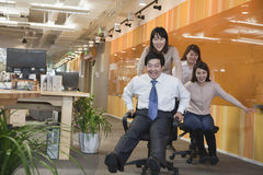 Businesswomen Pushing Her Colleagues in the Chair Stock Photo