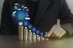 Businesswomen put money on pile of coins with green tree. And light bulb, concept in finance, loan and buying in business about car Royalty Free Stock Images