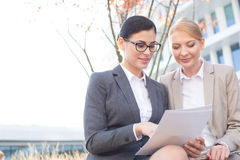 Businesswomen reading documents while sitting outdoors Royalty Free Stock Image