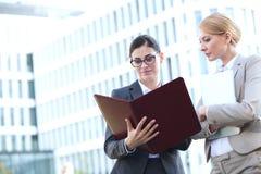 Businesswomen reading folder while standing outside office building Stock Photos