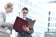 Businesswomen reading folder while standing outside office building Royalty Free Stock Images