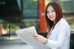 Businesswomen reading newspaer and holding mobile Stock Photography