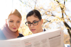 Businesswomen reading newspaper at park Royalty Free Stock Photography