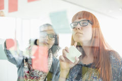 Businesswomen reading sticky notes on glass wall in creative office Stock Photography