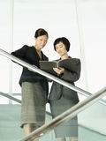 Businesswomen Reviewing Documents On Stairs Stock Photos