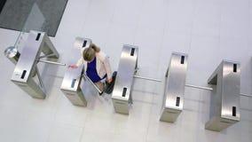 Businesswomen scanning their cards at turnstile gate. In office stock footage