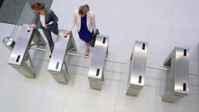 Businesswomen scanning their cards at turnstile gate. In office stock video footage