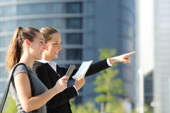 Businesswomen searching location with mobile gps and map. Two businesswomen searching location with mobile phone gps and paper map with office buildings in the royalty free stock images