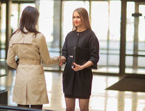 Businesswomen Shaking Hands In Modern Office Royalty Free Stock Image