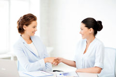 Businesswomen shaking hands in office. Picture of businesswomen shaking hands in office Royalty Free Stock Image