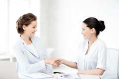 Businesswomen shaking hands in office Stock Image