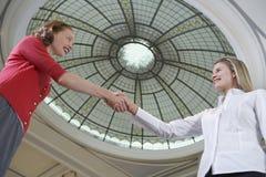 Businesswomen Shaking Hands Under Dome Stock Photos