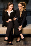 Businesswomen Sharing Info. Two Businesswomen Sharing Information on Mobile Device Outdoors in City Setting Stock Photo