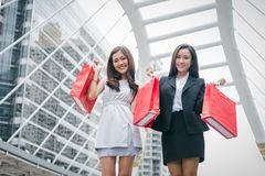 Businesswomen shopping at shopping mall and retail bag in urban. Rich happy shopper girls buying gift from product store in Black. Friday or Cyber Monday sale royalty free stock image