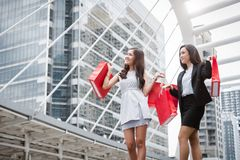 Businesswomen shopping at shopping mall and retail bag in urban. Rich happy shopper girls buying gift from product store in Black. Friday or Cyber Monday sale stock image