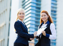 Businesswomen signing contract document Stock Images