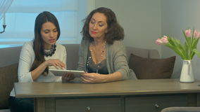 Businesswomen sit and have informal meeting looking at data on digital tablet together stock footage