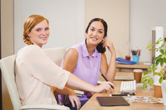 Businesswomen siting by desk Stock Photos