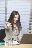 Businesswomen sitting at her desk smiling. And pointing finger Stock Photography