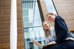 Businesswomen sitting with laptop in office premises Royalty Free Stock Image