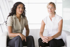 Businesswomen sitting in lobby Stock Image