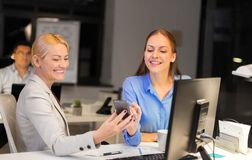 Businesswomen with smartphone late at night office stock photography