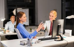 Businesswomen with smartphone late at night office royalty free stock images