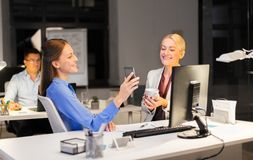 Businesswomen with smartphone late at night office stock image