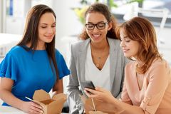 Businesswomen with smartphone at lunch in office royalty free stock photography