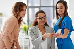 Businesswomen with smartphone working at office. Business, technology and people concept - businesswomen with smartphone working at office Royalty Free Stock Photo