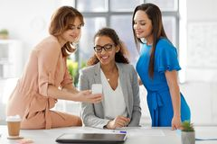 Businesswomen with smartphone working at office stock photo