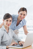 Businesswomen smiling at camera with laptop Stock Photo