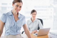 Businesswomen smiling at camera at their desk Royalty Free Stock Photography