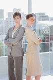 Businesswomen standing back to back and smiling Royalty Free Stock Image