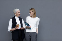 Businesswomen standing with digital tablet and coffee cup and smiling Stock Image