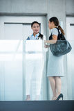 Businesswomen standing by elevator and having a conversation Stock Images
