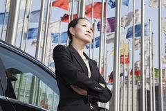 Businesswomen standing near car with flagpoles in background. Royalty Free Stock Image